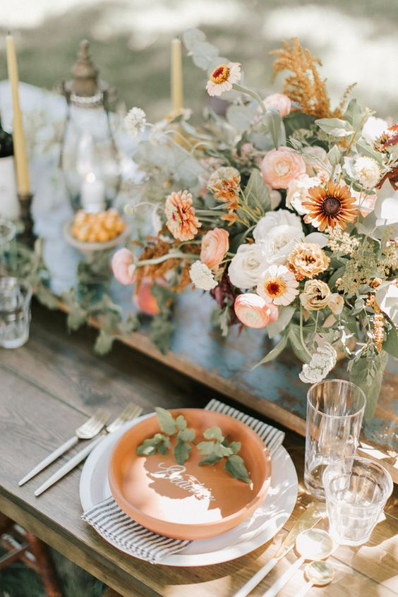 a delicate fall wedding centerpiece of orange and white blooms and lots of textural greenery
