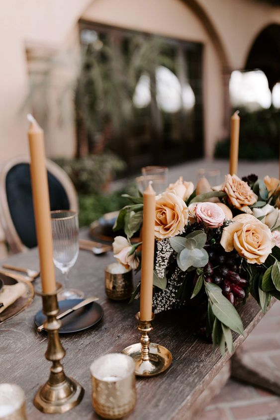 a delicate fall wedding centerpiece with blush and rust-colored blooms, greenery and grapes feels decadent
