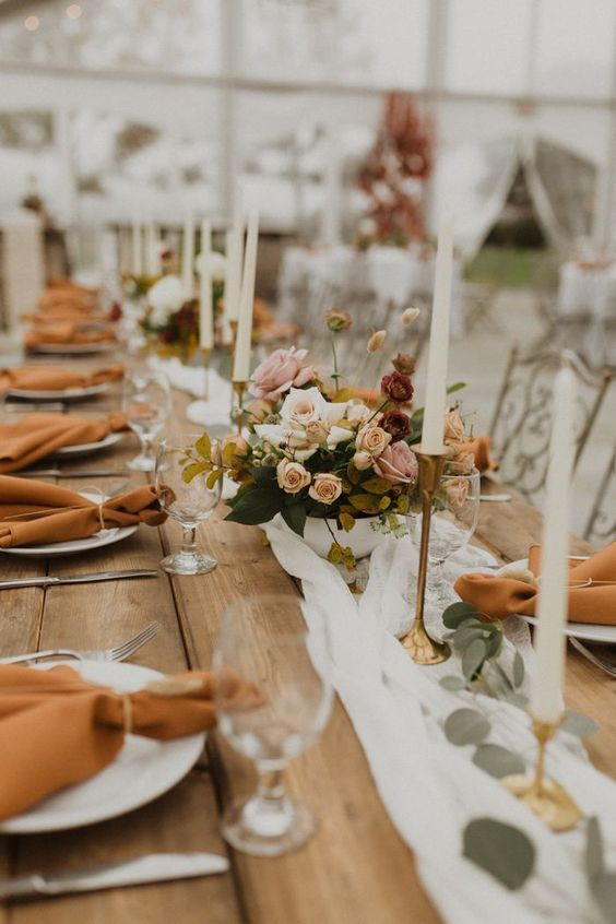 a delicate fall wedding tablescape with a neutral runner, rust napkins, pretty floral arrangements, greenery and candles in gold candleholders