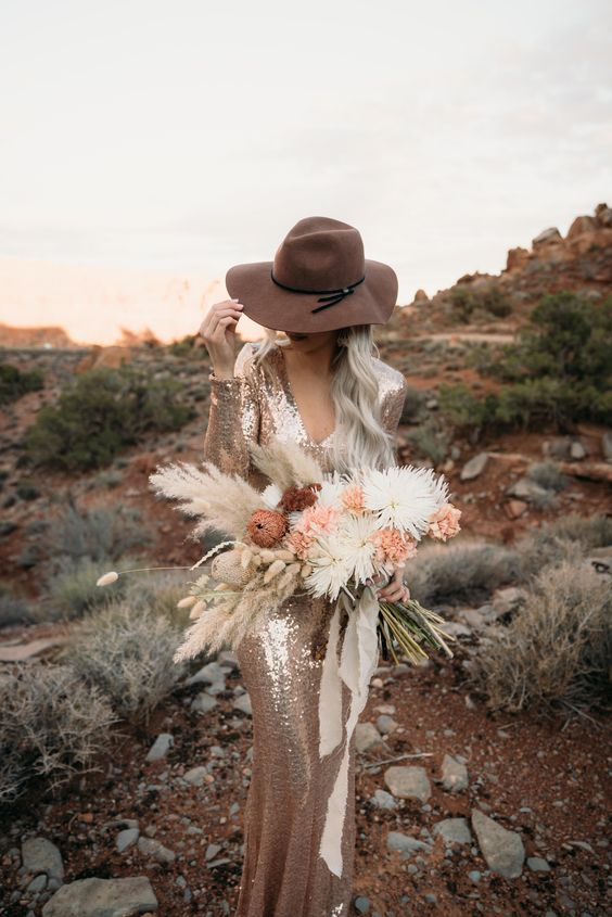 a desert elopement wedding dress with long sleeves, a V-neckline, a camel hat for a boho wedding