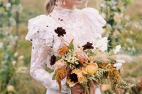 a dimensional and bright fall wedding bouquet of yellow and pink flowers, white blooms and deep purple ones, some greenery and ribbons