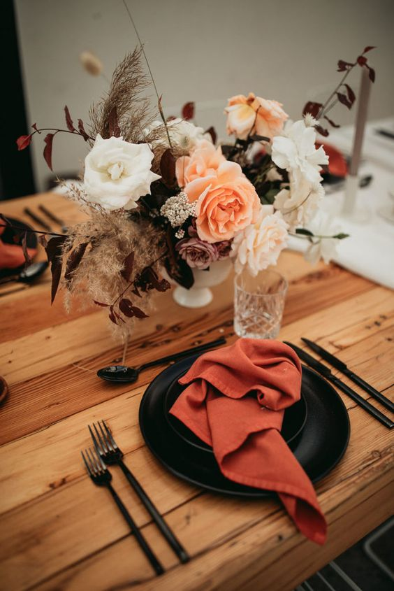a dramatic fall wedding tablescape with rust napkins, black plates, a pretty bold floral centerpiece, black cutlery and neutral candles