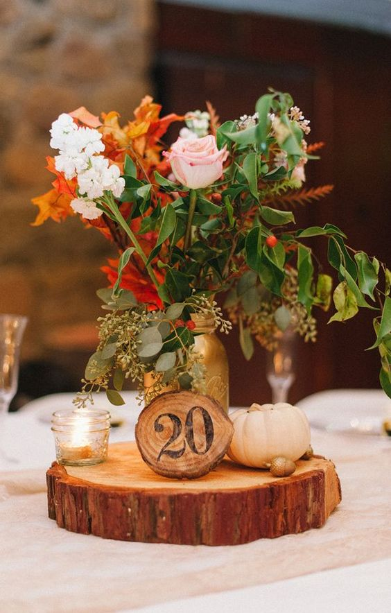 a fall centerpiece of a wood slice, acorns, pumpkins, candles, a wood slice table number and a bright floral arrangement