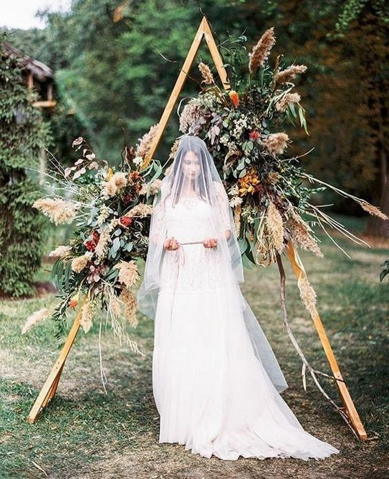a fall triangle wedding arch done with bold blooms, pampas grass, foliage and fall leaves