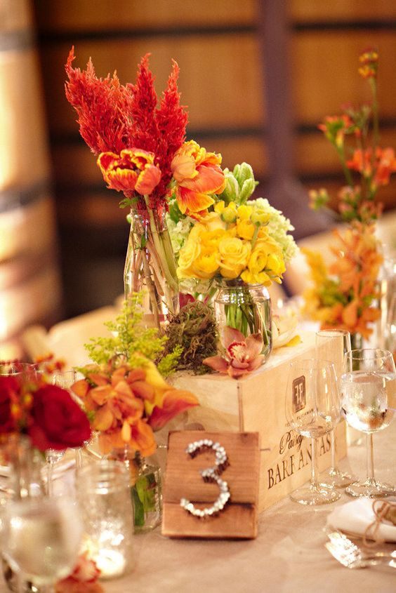 a fall vineyard table decoration of a crate, bright blooms in vases, moss and a table number with nails