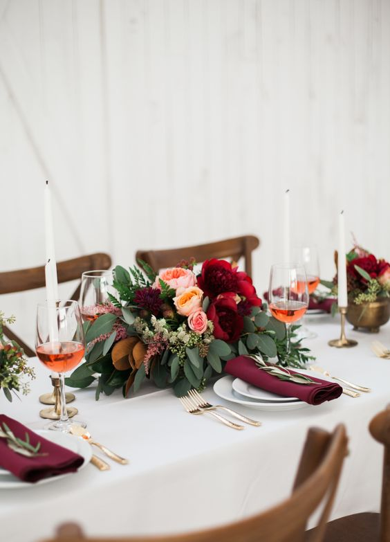 a fall wedding centerpiece of lush greeneyr, blush and peachy blooms, burgundy flowers and white candles