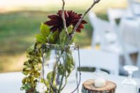 a fall wedding centerpiece with a wood slice, pinecones, greenery, branches and burgundy blooms looks very cozy and rustic