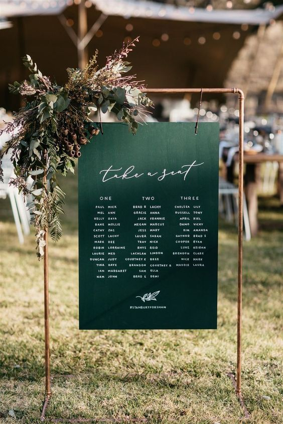 a fall wedding seating chart of a copper frame, a green chart hanging and lush greenery and acorns is lovely