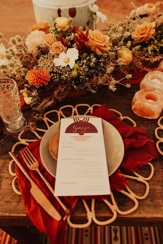 a fantastic boho wedding tablescape with a bold orange, rust, burgundy, peachy floral centerpiece, quartz candleholders, red napkins and rattan placemats