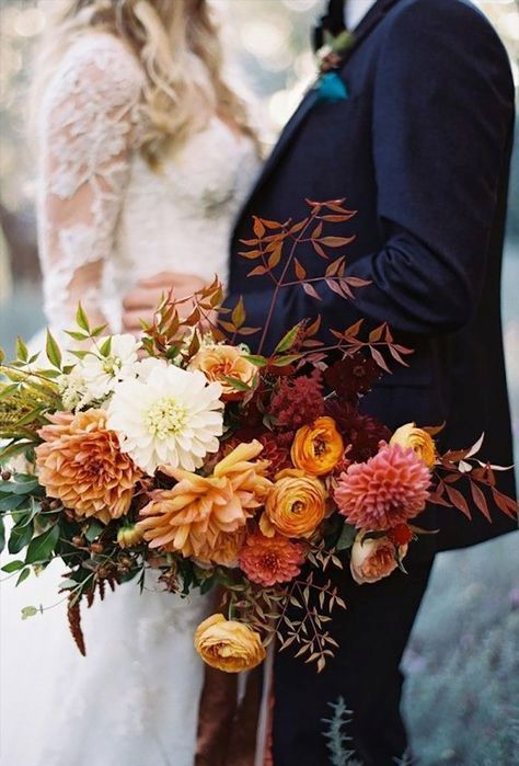 a fantastic colorful fall wedding bouquet of orange, rust, pink, white and burgundy flowers, greenery and bold fall foliage