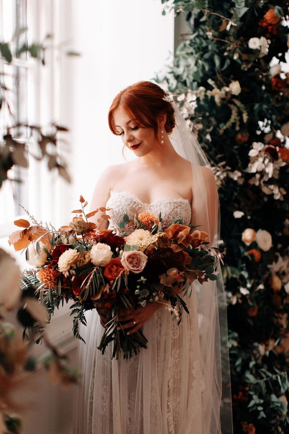 a fantastic lush and dimensional wedding bouquet of pink, blush, burgundy, rust blooms, greenery and berries plus bold fall leaves is gorgeous