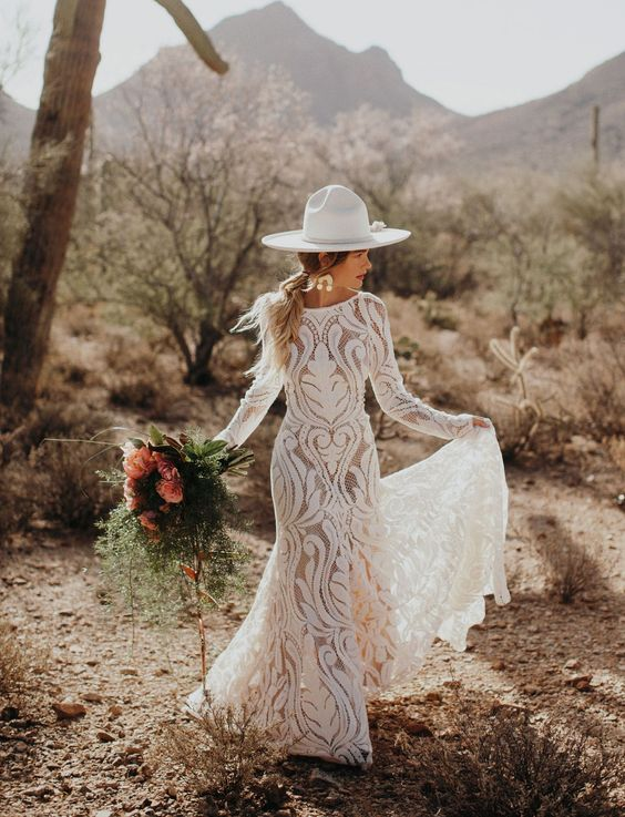 a fitting boho lace wedidng gown with a high neckline and long sleeves, statement earrings and a white hat for a boho elopement