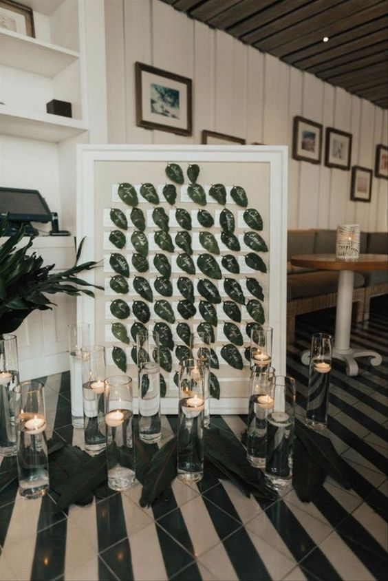 a framed seating chart with leaves and floating candles is a very refined and chic idea for the fall
