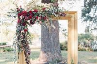a gold frame decorated with greenery, foliage and burgundy blooms plus candle lanterns for an outdoor fall ceremony