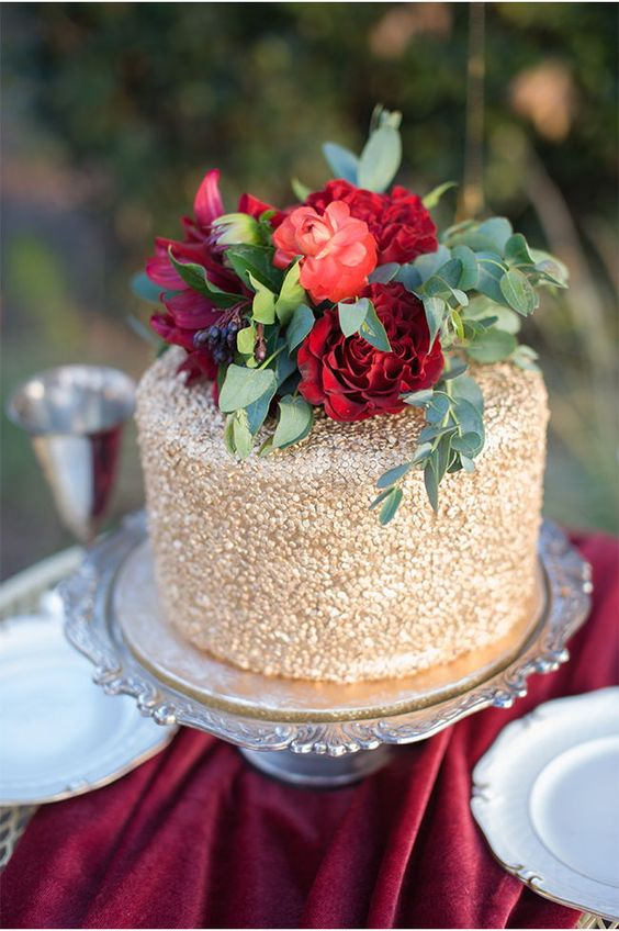 a gold wedding cake topped with red and burgundy blooms plus greenery and berries for the fall