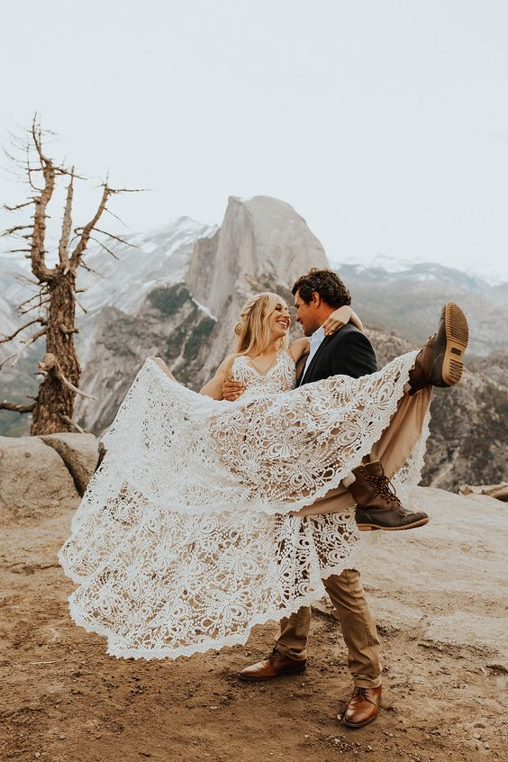 a gorgeous boho lace wedding dress with thick straps and a V-neckline, hiking boots for a mountain elopement