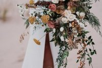 a gorgeous dimensional fall wedding bouquet of white, pink and rust blooms, greenery, berries, cascading branches and greenery is cool for a boho bride