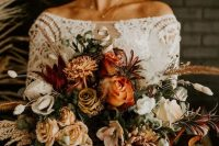 a gorgeous fall wedding bouquet of rust, light yellow, white and burgundy blooms, greenery, buny tails and dried grasses is a lovely solution for a boho bride