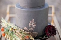 a grey fall wedding cake with copper patterns and dark blooms plus dried herbs and blooms