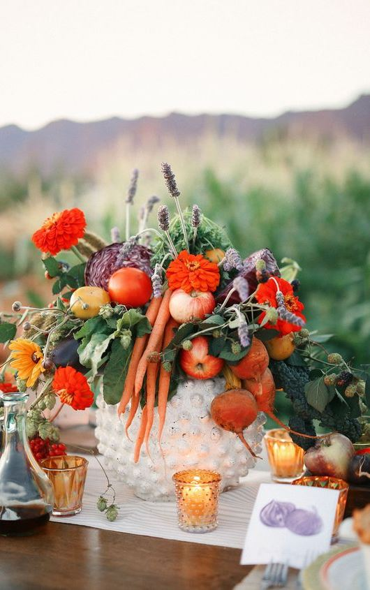 a harvest wedding centerpiece of a white bowl, bright red and orange blooms, lavender, greenery, apples, carrots and beets