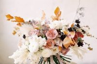 a jaw-dropping delicate-colored fall wedding bouquet of white, pink, rust blooms and fall-colored leaves and ribbons is very chic