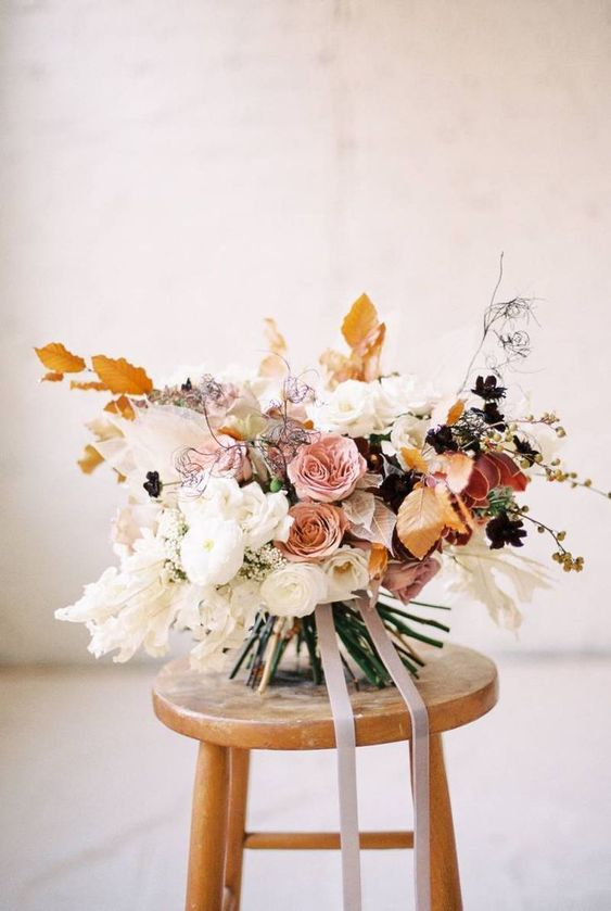 a jaw dropping delicate colored fall wedding bouquet of white, pink, rust blooms and fall colored leaves and ribbons is very chic