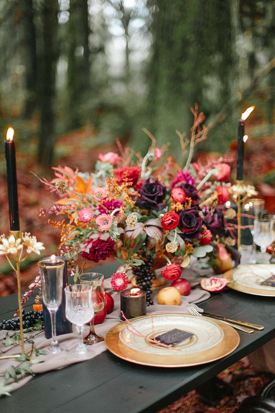 a jewel tone wedding centerpiece with lots of greenery, red, pink and purple blooms and grapes, candles and apples on the table