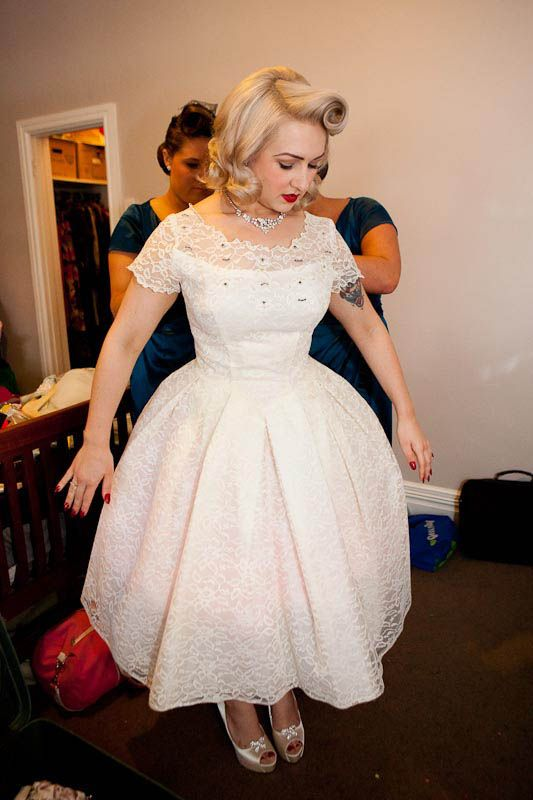 a lace tea length wedding dress with an illusion neckline and short sleeves plus peep toe shoes and a rockabilly hairstyle