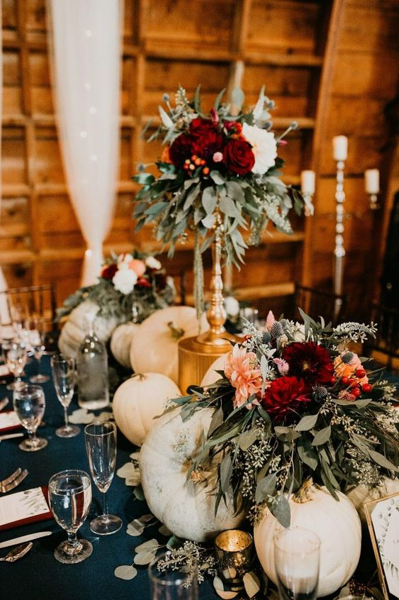 a large fall wedding centerpiece of white pumpkins, white, blush and burgundy blooms and lots of eucalyptus