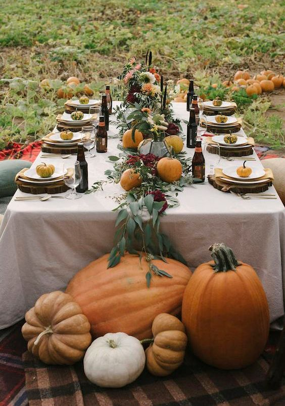 a leafy table runner with burgundy blooms and fresh pumpkins, wood slices, plates, pumpkins and beer bottles for a fall wedding