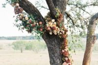 a living tree decorated with neutral and burgundy blooms and foliage for an outdoor fall wedding ceremony