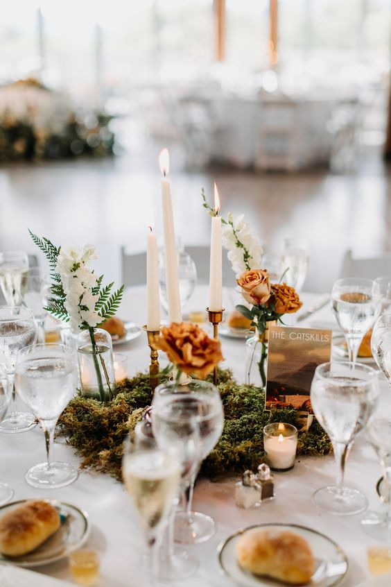 a lovely and chic fall wedding tablescape with a moss, white and rust blooms centerpiece, candles, white porcelain and glasses