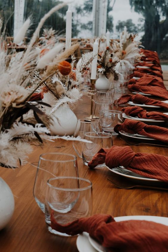 a lovely boho wedding tablescape with an uncovered table, rust napkins, white candles, white vases with grasses and rust blooms
