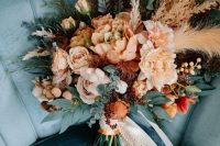 a lovely fall-colored wedding bouquet of blush, pink, rust blooms, greenery, grasses and berries, long lace ribbons is amazing for a boho wedding