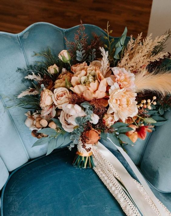 a lovely fall colored wedding bouquet of blush, pink, rust blooms, greenery, grasses and berries, long lace ribbons is amazing for a boho wedding