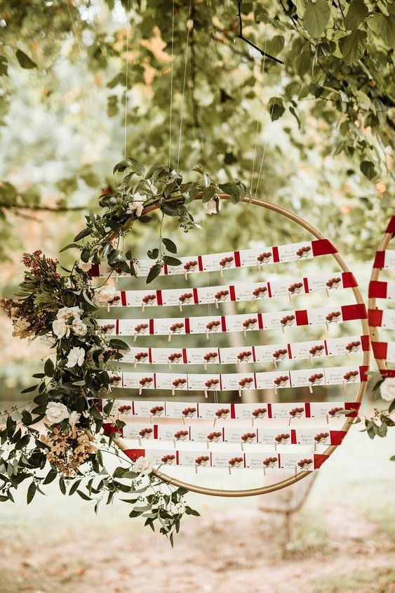 a lovely flal or winter seating chart of an oversized embroidery hoop, greenery and neutral blooms, cards with berries attached to red fabric straps