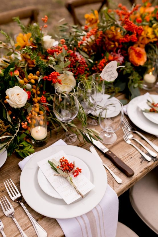 a lovely harvest wedding tablescape with bold blooms, berries, fruits, greenery, white plates and napkins, menus and cards