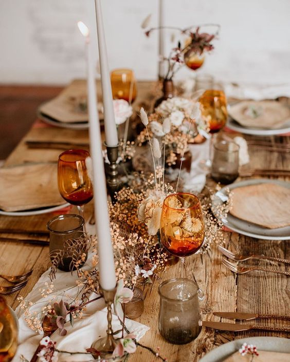 a lovely wedding tablescape with amber glasses, copper cutlery, grey glasses and plates and dried blooms and leaves