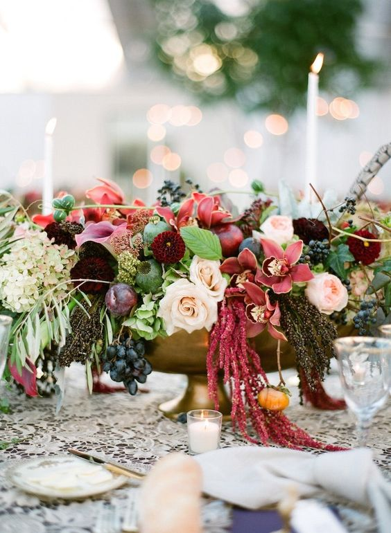 a lush and colorful fall wedding centerpiece of pink, mauve, burgundy, blush blooms, greenery and grapes plus a feather