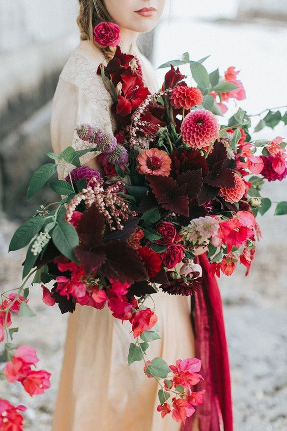 a lush and dimensional wedding bouquet in burgundy, red, pink blooms and greenery