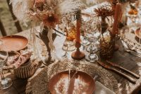 a lush boho wedding tablescape with copper plates, candles and blooms, cutlery, raffia placemats, neutral linens and dired grasses