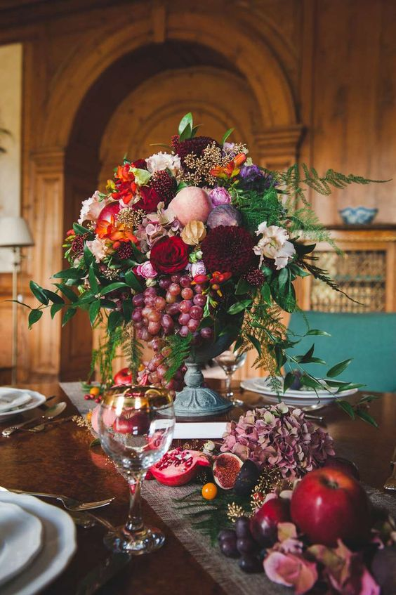 a lush fall wedding centerpiece of a vintage urn, red, burgundy, purple, orange and pink blooms, greenery and grapes