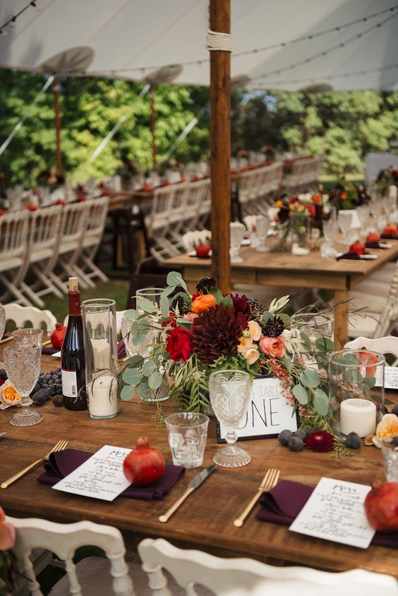 a lush fall wedding centerpiece of burgundy, red and blush blooms, grapes, plums and eucalyptus and candles