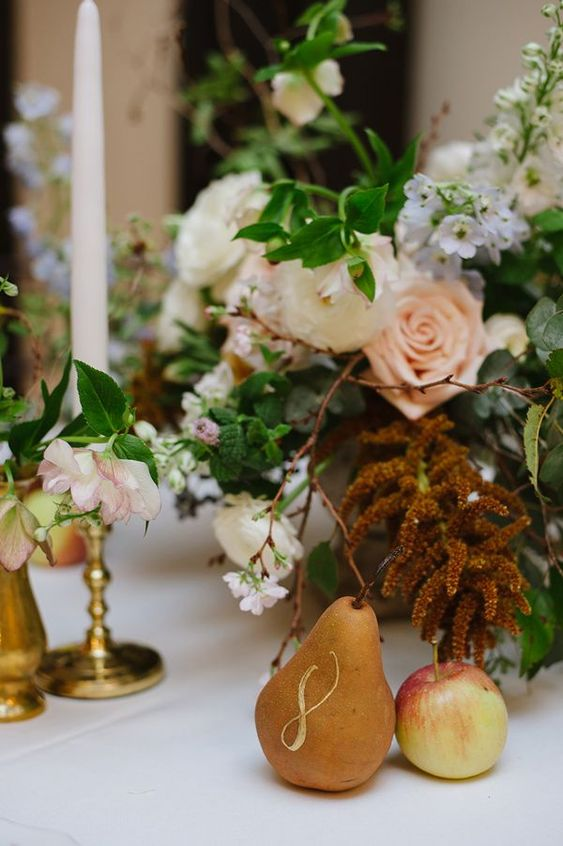a lush floral centerpiece and an elegant table number on a pear make up a chic look for a fall wedding