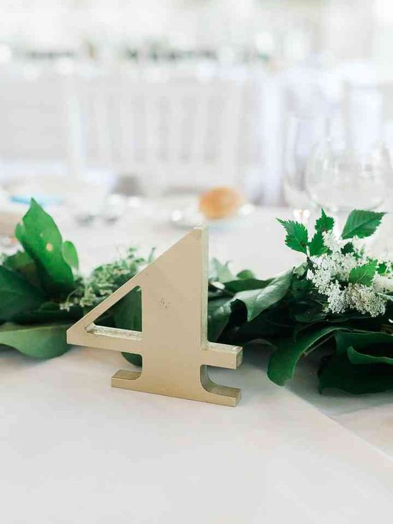 a lush greenery garland with wildflowers and a simple metal table number for modern fall wedding decor