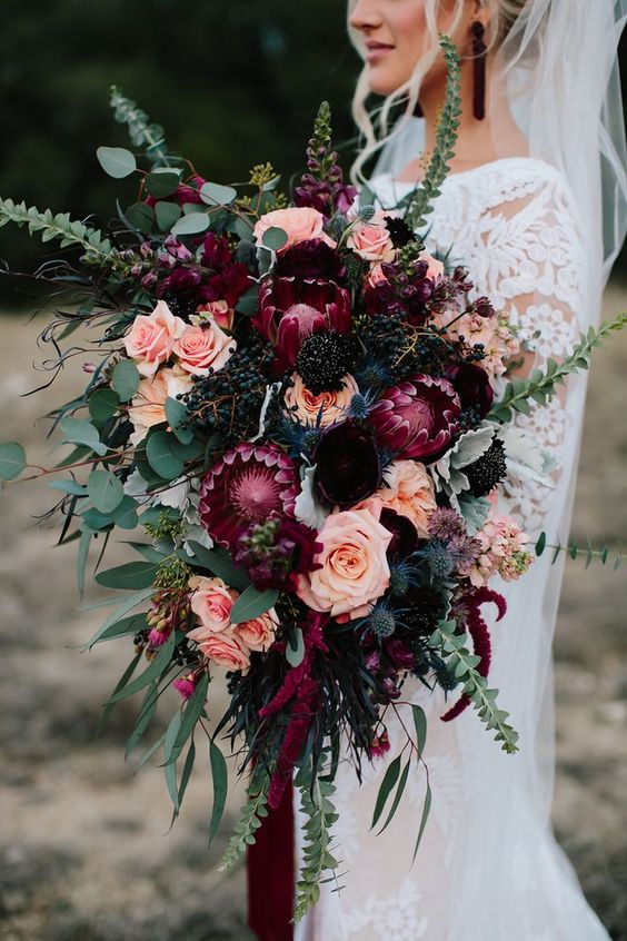 a luxurious fall wedding bouquet of pink, fuchsia, deep purple and black blooms, berries and greenery plus ribbons for a decadent bridal look