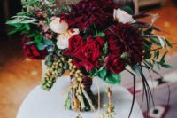 a luxurious wedding bouquet with berries hanging down, burgundy and blush blooms and foliage