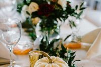 a mini pumpkin with a table number, greenery and candles for fall wedidng table styling