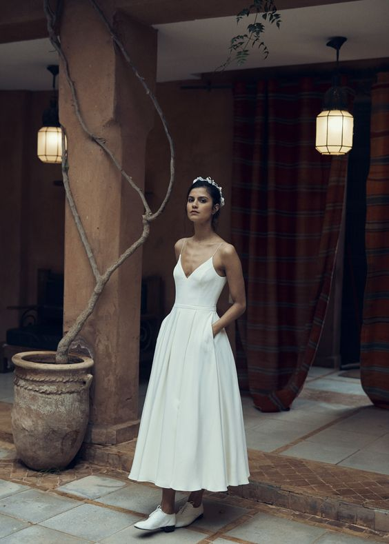a minimalist A-line tea length wedding dress with a pleated skirt and pockets, a deep neckline and classy shoes