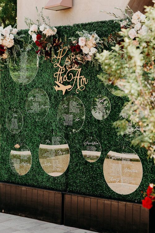 a modern fall wedding seating chart of a boxwood wall, bright and blush florals and acrylic circles is awesome